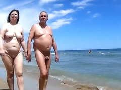 Older people walk around the beach completely naked
